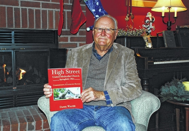 "Daniel Walter holds a copy of his first published book, ""High Street United Methodist Church: A Comprehensive, Illustrated History,"" inside his Urbana home."