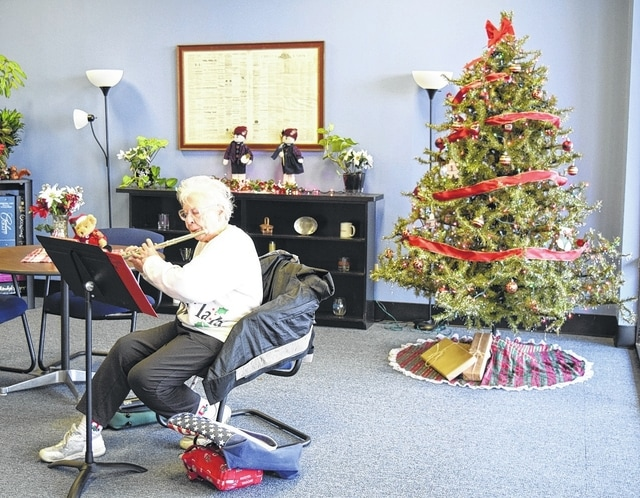 Dr. Janet Ebert of Urbana serenades <em>Daily Citizen</em> staff with Christmas songs on her flute. Ebert is known for touring the community to spread Christmas cheer with her flute during the holidays.