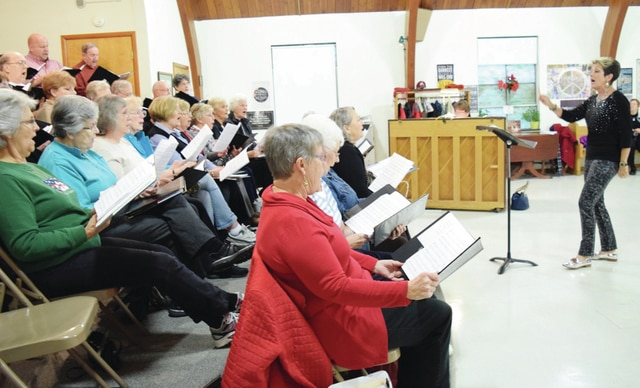 Urbana Champaign County Senior Center Choir Director Jacquelyn Howell, at right, leads a practice with the Guys N Dolls on Monday for the upcoming Christmas program. Her friend Sue Maurice is at the piano. Howell and Maurice are retiring from organizing the program, though they will continue to work together at their church, the Urbana United Methodist Church.