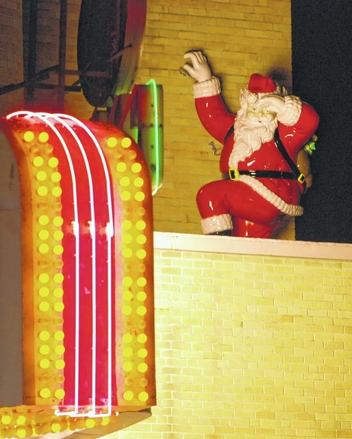 The large, vintage Santa statue pictured in this photo climbing the facade of the Gloria near the marquee is part of the renovation of the theater and its many historic parts.