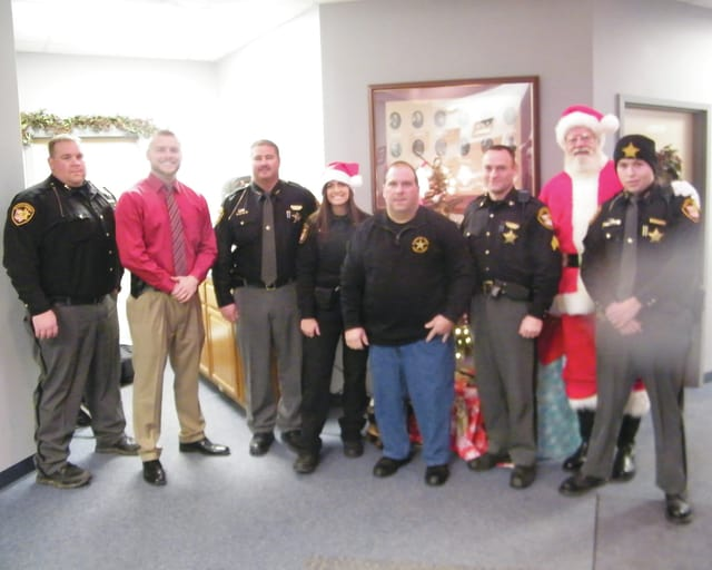Members of the Champaign County Sheriff's Office were assisted by Santa Claus in delivering Christmas presents to over 50 children in the Champaign County area Tuesday as part of the Wipe out a Blue Christmas project.