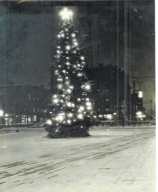 This 1908 Whitham nighttime photo shows the decorated Christmas tree near the middle of the square of Urbana.