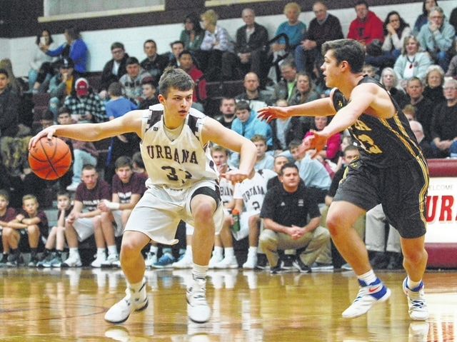 Urbana's Riley Emmons (left) holds off a Kettering Alter defender at mid-court during Tuesday night's game at UHS.