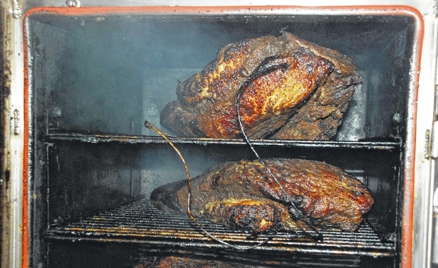 Beef brisket, shown inside the smoker at Big Willie's Smokehouse, is one of the restaurant's staple meats being offered daily (Tuesday through Saturday) at 23 Monument Square in downtown Urbana.