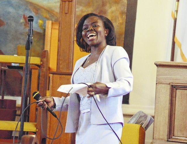 Joyce Ofori leads the congregation in song during St. Paul's AME Church's Dr. Martin Luther King celebration service in Urbana on Sunday.