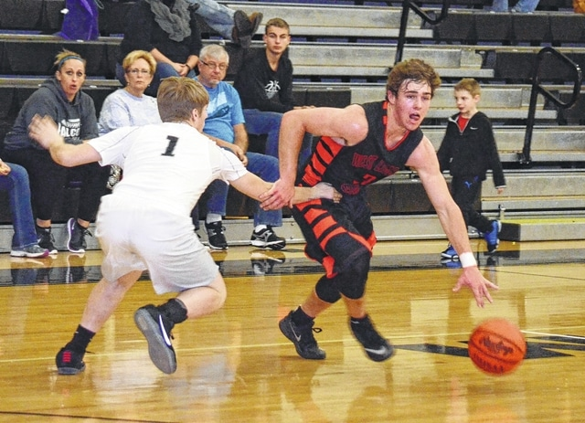 West Liberty-Salem's Kannon Stillings (3) makes a move to get past his defender on Tuesday at Graham, while Tristen Henry (1) does his best to stay in front.
