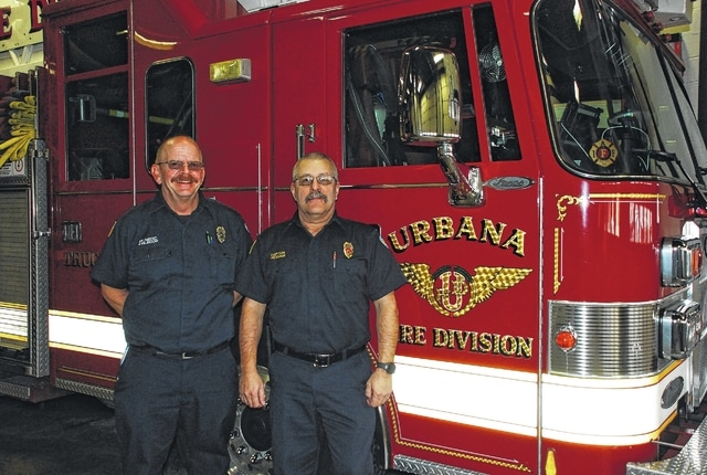 Urbana Fire Division Capt. James Freeman, right, and Firefighter/Paramedic Brett Evilsizor, left, pose in front of the city's ladder truck on Thursday. Freeman retired on Friday after 31 years of service, while Evilsizor will do the same later this month after 30 years of service.
