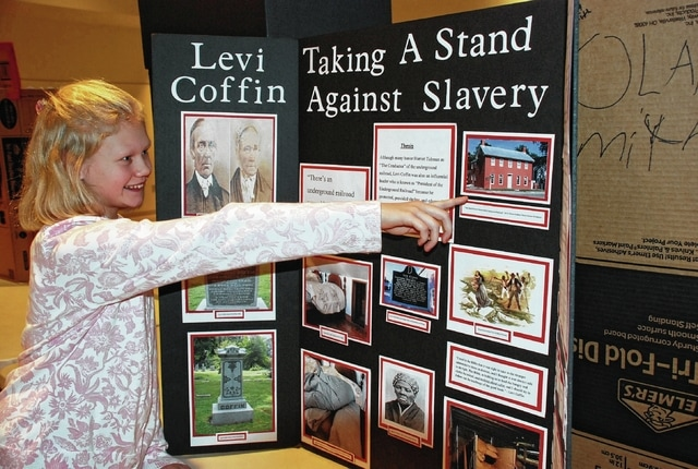 Urbana Junior High student Lillian Matteson explains her history project about abolitionist Levi Coffin during Tuesday's Urbana Junior High History Day at the Urbana University Student Center. Coffin was an active leader in the Underground Railroad in Indiana and Ohio. Matteson's display was one of three individual winners for the seventh grade competition.