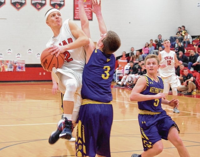 Triad's Austin Bails (2) scales Mechanicsburg's Logan Hurst (3) to attempt a layup in transition on Tuesday, while the Indians' Mack DeLong (5) trails the play.