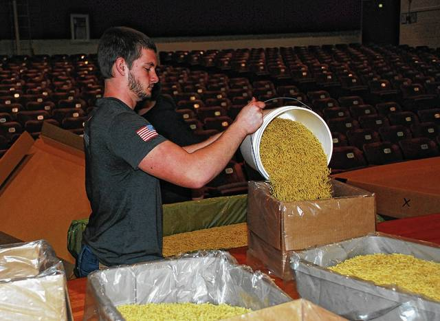 Urbana High School senior John Cordle transfers macaroni noodles from a large box used for shipping to a smaller box so fellow Future Farmers of America (FFA) students can package individual meals during Thursday's Meals of Hope Food Packaging Event held in the UHS gymnasium.