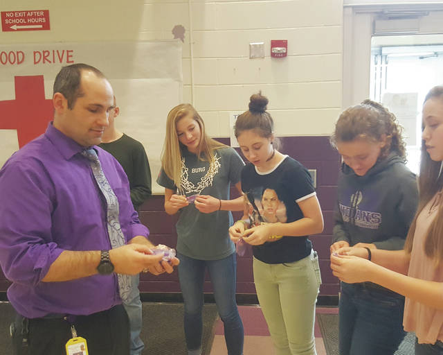 Mechanicsburg High School Principal Paul Hershberger Jr. handed out wristbands to students promoting the Crisis Text Line. The text line is a free, anonymous service aimed at anyone who may be struggling with suicide or addiction.