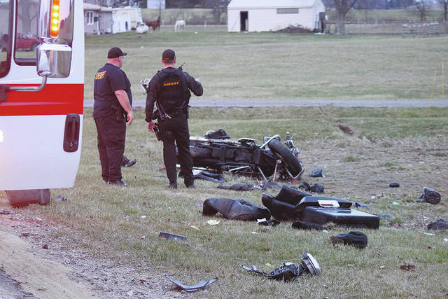 Investigators and first responders stand near a motorcycle crashed just off state Route 245 on Saturday evening.