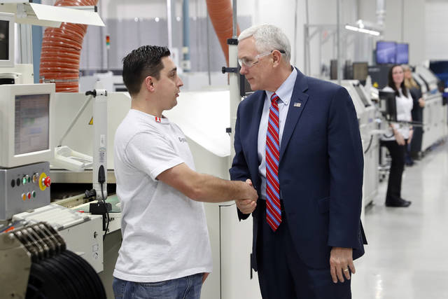 Vice President Mike Pence, right, shakes hands with an employee as he tours the DynaLab, Inc. facility, Saturday, April 1, 2017, in Reynoldsburg, Ohio.  (AP Photo/John Minchillo)