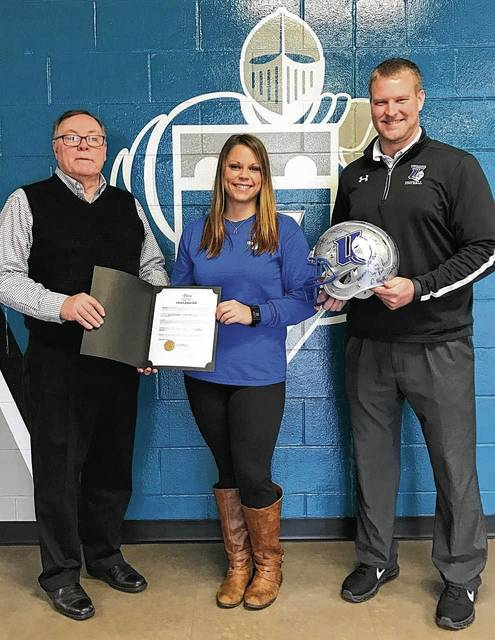 Champaign Family Y Health Enhancement Director Jennifer Post stands between Urbana Mayor Bill Bean and UU Head Football Coach Tyler Haines, who holds a Blue Knights helmet autographed by UU football players and coaches. The helmet will be raffled at 11:30 a.m. on April 22 at the UU Grimes Center during Healthy Kids Day. To enter a raffle ticket, children must attend the 4 p.m. April 21 football game. Admission to the game is free for all. Post will hand out free raffle tickets by the entrance to the UU football game.