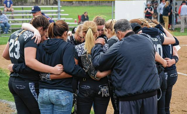 Graham's softball team huddles for a prayer before Tuesday's game against Greenon. Tuesday's ritual was especially poignant, as Graham pitcher Madison Bryant was hit in the head by an errant throw while warming up and was unable to participate.