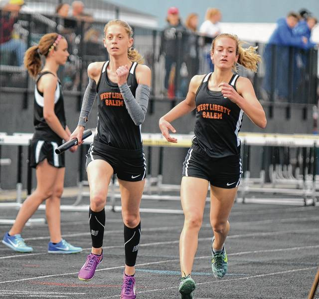 West Liberty-Salem's Katie Hartsel (left) takes the baton from Grace Adams in the girls' 4x800 relay race at the Graham Invitational on Thursday.