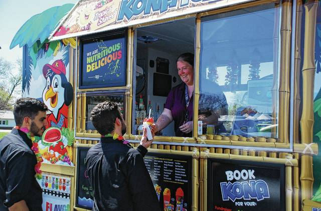 "Sarah Lay, owner of Kona Ice of Troy, serves up free shaved ice to Justin Lord, right, and Anthony Baglione, left, on Tuesday at the Champaign County Library. Lord and Baglione, who work for L.A. Catering out of Columbus, were in Urbana for a Meals on Wheels event at the library and couldn't pass up a free treat. Lay said she was handing out free shaved ice to the public as part of Kona Ice's National Chill Out Day, held every year on Tax Day as a way for the company to help Americans ""chill out and relax"" during one of the most stressful days of the year."