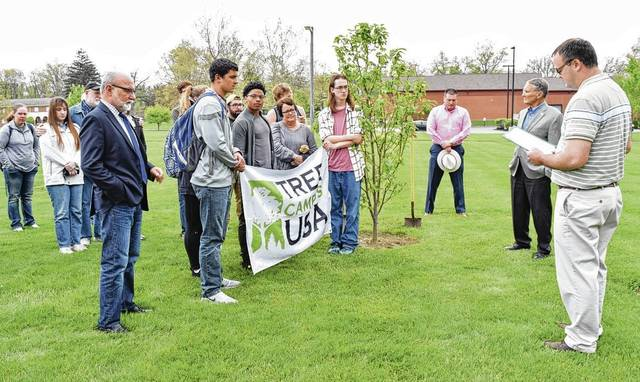 Urbana University students and staff, and City of Urbana Community Development Manager Doug Crabill, right, recognize Arbor Day with a tree planting and city proclamation near the Lewis and Jean Moore Center on campus. This is the university's fifth year of being an Arbor Day Foundation Tree Campus USA, and the 15th year of the city being recognized as a Tree City USA by the same group. Two trees were planted at Urbana University Friday – one, n memory of alumna Jill Smith, Director of London Prison for Urbana University programs, English instructor and wife of Tom Smith (faculty of 25 years) who recently retired. The second tree planted was in memory of firefighter Martin Frazee, son of Mary Anne Frazee (faculty for 25 years). Martin died at age 33 and was an organ donor.