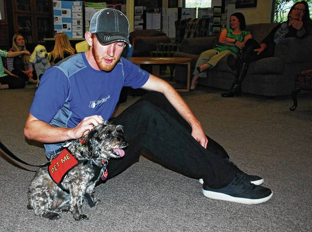 Bryce Philabaum, an Urbana University freshman majoring in accounting, stopped by the university's Swedenborg Memorial Library on Tuesday to spend a few minutes with Tickles, a female schnauzer/terrier mix. Urbana resident Nancy Sleeper, Tickles' owner, has organized pet therapy sessions at UU for the past five years to provide students an opportunity to take a break from studying for final exams to visit with various K9s.