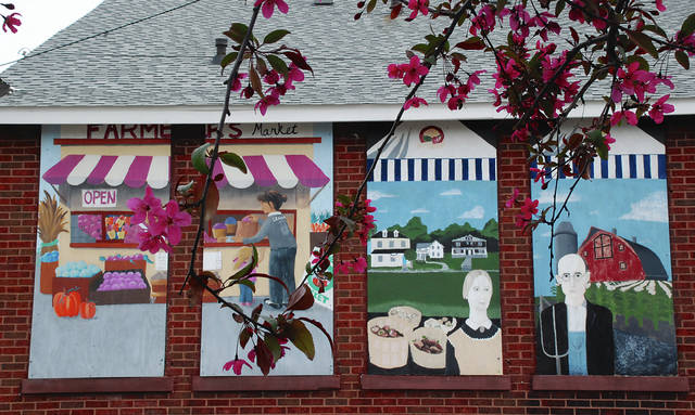 The Champaign County Farmers Market is located on the corner of Market and Locust streets in Urbana, behind the Municipal Building. Spring blooming trees are shown framing the paintings that provide a backdrop for the market each year. The market opens the first Saturday in May.