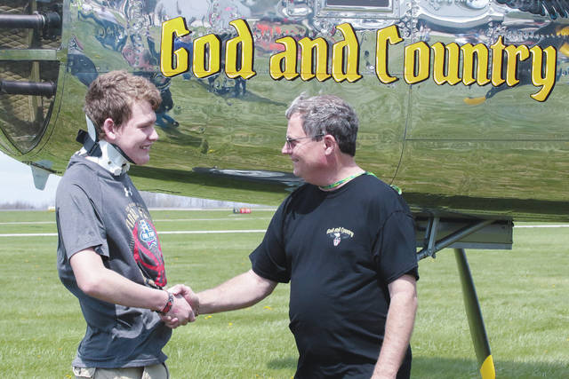 West Liberty-Salem student Logan Cole, left, shakes hands with B-25 pilot Scott Glover at Grimes Field.