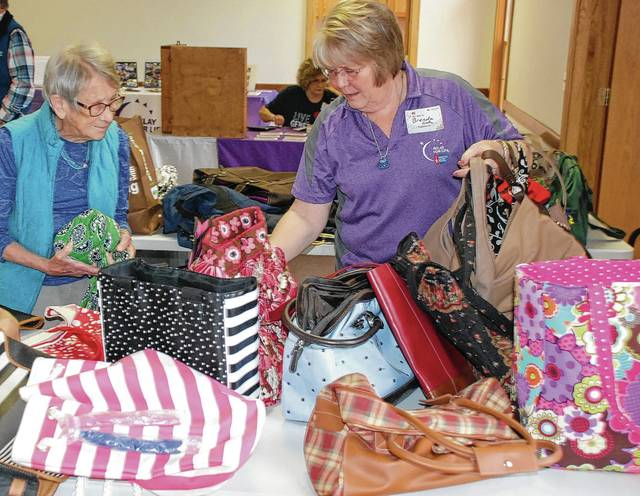 "Mary Pollock (left) and Brenda Cook help organize the annual ""Old Bag Sale"" at the Evans-Purk Fellowship Hall in St. Paris on Sunday. The fundraiser has become a tradition in the preparations for sponsoring a team in the Relay for Life event at the Champaign County Fairgrounds each May. Relay for Life benefits the American Cancer Society."
