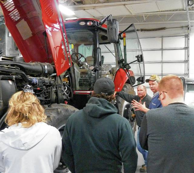Students and instructors gather to learn around a new Case IH 240CVT tractor equipped with precision guidance.