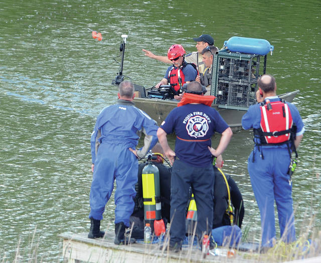 Mike Ullery | Daily Call A rescue boat team member from Ohio Department of Natural Rescoures tosses a marker buoy into a pond as emergency personnel search for a young drowning victim in a Piqua pond on Sunday.