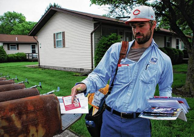 Urbana mail carrier Phillip Forsythe places a Stamp Out Hunger Food Drive postcard reminder into a mailbox on North Jefferson Avenue on Thursday. Organized by the National Association of Letter Carriers, the food drive will take place Saturday, May 13. During their regular Saturday routes, city mail carriers will pick up bags of non-perishable food items from any residences wishing to participate. Food donations can also be dropped off between 8:30 a.m. and 12:30 p.m. on Saturday at the Urbana Post Office, 200 S. Main St.