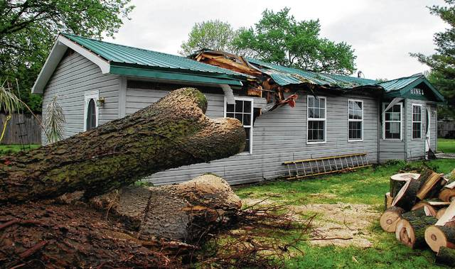 Pictured is what remains of a large tree that fell on the Hines' residence on Monday. According to the property owners, the home at 318 Grand Ave. in Urbana is a complete loss and will need to be leveled.