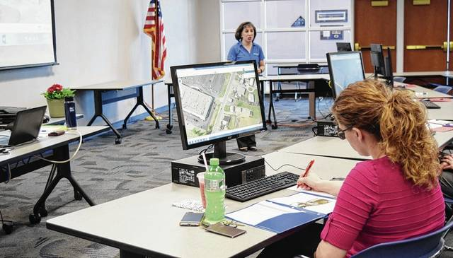 Champaign County 911 Director Vannessa Haley listens to Pictometry Eagleview presenter Laura Mondo teach county workers to use the program Tuesday. The new Pictometry program can be used by a variety of agencies that need to look at county properties in detail.