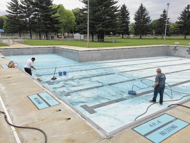 Charles Williams and Bob Pullins of the Champaign Family YMCA do preparation work on the city pool this spring.