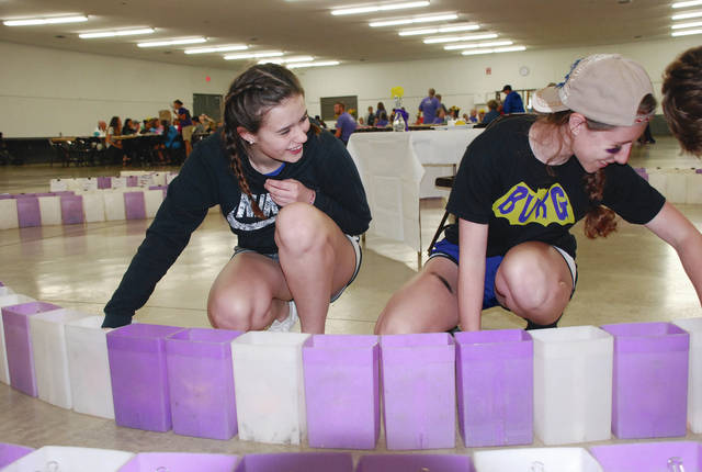 Mechanicsburg students Kerrigan Cushman (left) and Emma Wilson prepare luminaries during Friday night's Relay for Life at the Champaign County Fairgrounds. Late afternoon thunderstorms moved most of the events indoors.