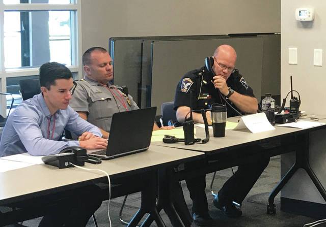 From left, county Health Commissioner Gabe Jones, Highway Patrol Trooper Brian Allen and Mechanicsburg Police Chief John Alexander operate the simulated operations center during the June 6 hazmat drill.