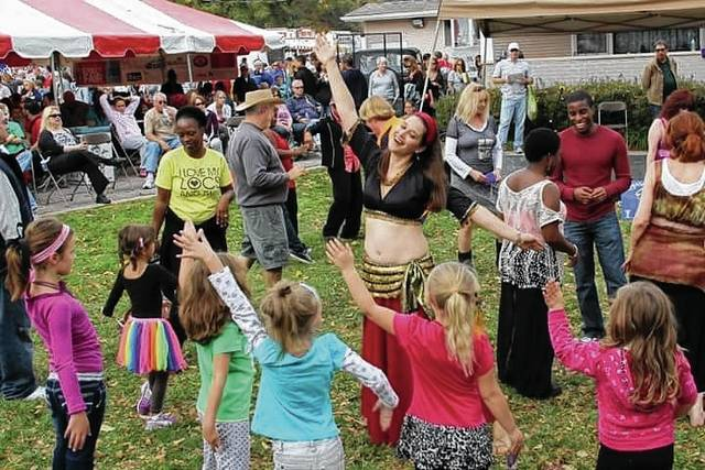 A belly dancer of the group Egyptian Breeze demonstrates moves to young observers during a past Yellow Springs Street Fair. The group is one of several that will entertain at this year's event.