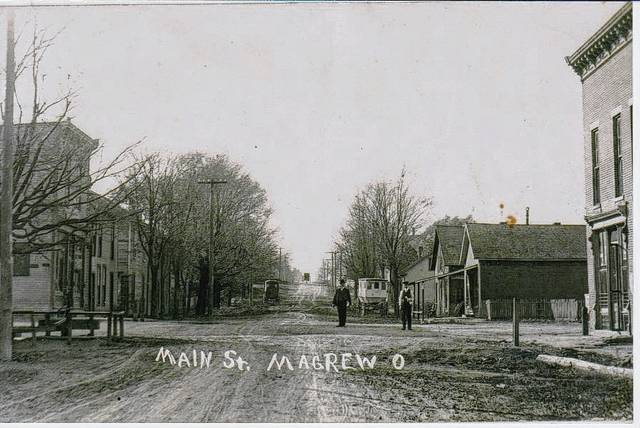 Then - This is a photo of Main Street, Magrew (Westville), looking west at the intersection of what is now U.S. Route 36 and state Route 560. The former Baker Grocery is on the southwest corner. The upper story of the building had an auditorium with a stage. The Grange Hall (1876) is on the northeast corner. It is not known when this photo was taken. The absence of cars suggests early 1900. Notice the buggy proceeding up the hill. Westville was platted in 1815 by Archibald Magrew. The historical society has 1908 and 1909 postcards post marked Magrew. It is not known during which time period the community was officially designated Magrew.