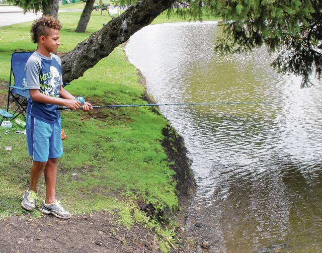 Twelve-year-old Andre Jones tries his luck along the banks of the pond at Melvin Miller Park in Urbana during a recent afternoon. A summer afternoon fishing helps fill the void when school isn't in session.