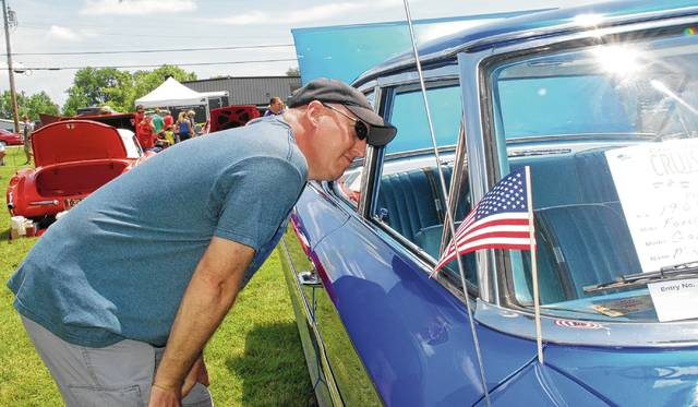 Chris Snyder of Dayton peeks into the window of a 1964 Galaxie 500 during the 20th Annual Champaign Cruisers Firecracker Car, Truck and Bike Show near the Urbana airport on Tuesday. Each year the Cruisers host the show to raise money for local causes. The Galaxie 500 is owned by Mike Purtee. In addition to the car show, fireworks, a concert and a chicken barbecue were also part of the big event at Grimes Field for July 4.