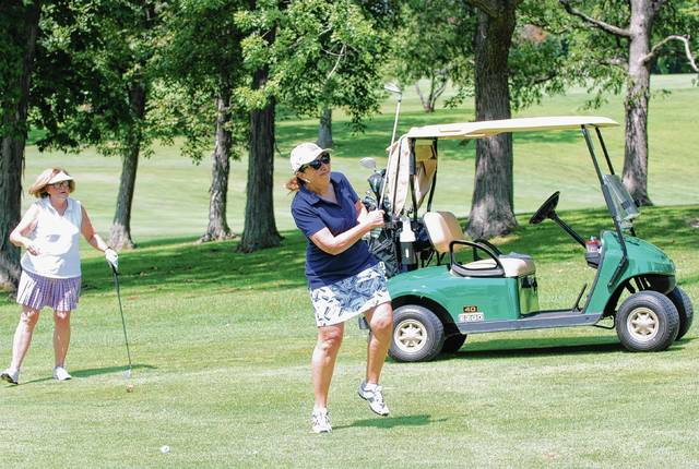 Cheryl Cave hits an approach shot to the green as Susie Dietz looks on during Wednesday's BBCO.