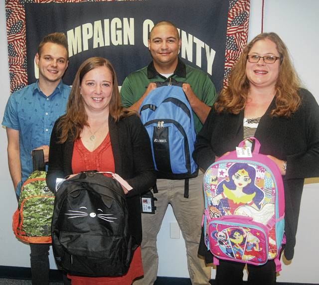 """Members of the Champaign County Department of Job and Family Services' children services team, from left, Adam Allbright, Mandy Wilber, Stephen Allen and Kristina Hawkey, hold a few of the many backpacks donated to CCDJFS by the Northern Miami Valley Episcopal Cluster. The cluster, which includes the Church of Our Saviour in Mechanicsburg and the Church of the Epiphany in Urbana, donates the backpacks to be given to foster children. Church members pack the backpacks with age-appropriate quilts or blankets, journals, toothbrushes and toothpaste, wash cloths, books, puzzles, toys and other items to comfort them as they enter foster care. """"We thank the churches for their thoughtfulness in making a positive difference in the lives of these children at a difficult time,"""" said Stacy Cox, social services administrator of CCDJFS."""
