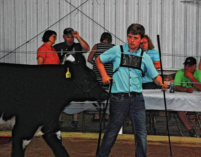 Avery McGuire parades his Grand Champion Steer around the show ring on Wednesday at the Champaign County Fairgrounds.