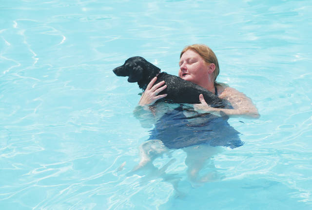 Fido's Swimfest drew a steady stream of dogs and their owners to the city pool on Sunday. The swimfest for dogs is becoming an annual event that occurs after the pools close to human customers for the season. In photo, Amber Queen and her dog Bella enjoy the refreshing swim on a hot, August day.