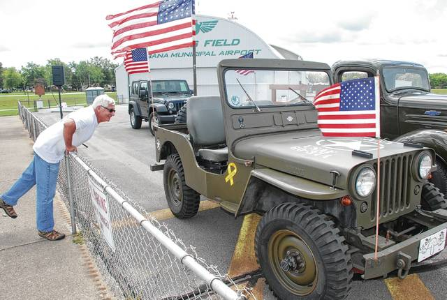 Kenny Lake checks out a USAF Jeep at Grimes Field on Friday. He was waiting to catch a glimpse of the barnstorming biplanes and other aircraft flying into Urbana for the Mid-Eastern Regional Fly In (MERFI), which will be in full swing today. This is the 50th anniversary of MERFI. For more information on the event and today's schedule, visit merfiurbana.org.