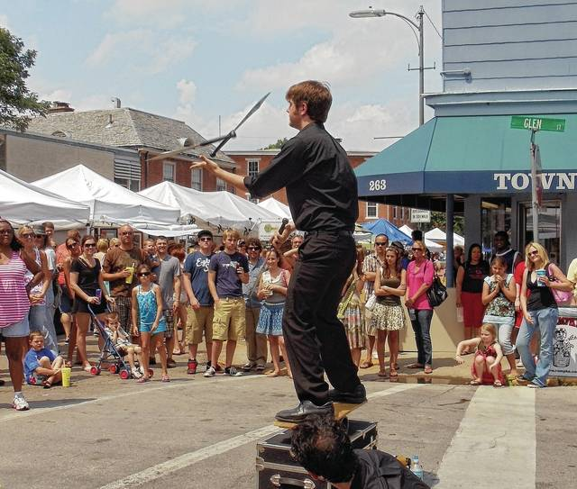 A crowd watches a juggling street performer during a previous Yellow Springs Street Fair.