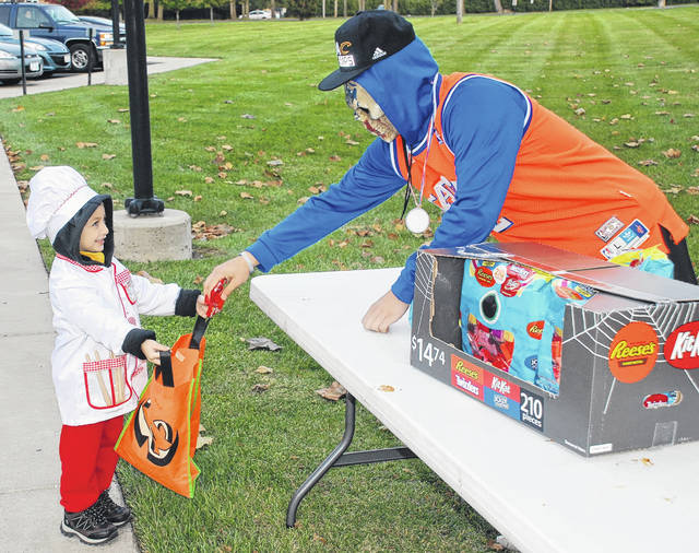 Urbana and several other municipalities in Champaign County hosted Beggars Night on Tuesday. Urbana University offered candy to children who visited the lawn near the Student Center. In the photo, 4-year-old Leo Duer accepts candy from a masked student who volunteered to help treat the little trick-or-treaters who visited.