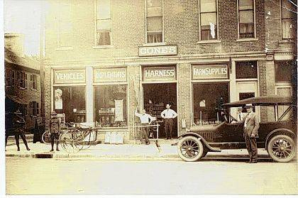 "When Cone's moved to the new Easton Building in 1895, its main product lines were agriculture implements and buggies. This photograph would seem to date from the World War I era based on the car in the foreground and the uniforms of the men to the left of the picture. The hitching post in front of the building and the prominence of the ""Harness"" sign over the door tells us that the car as not yet entirely replaced the horse. The lace curtains in the second floor windows look residential."