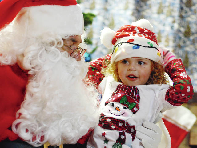 Anierra Greene, age 3 1/2, holds on to her lighted Christmas cap while giving Santa her list on the first night of Santa Land at The Gloria Theatre.