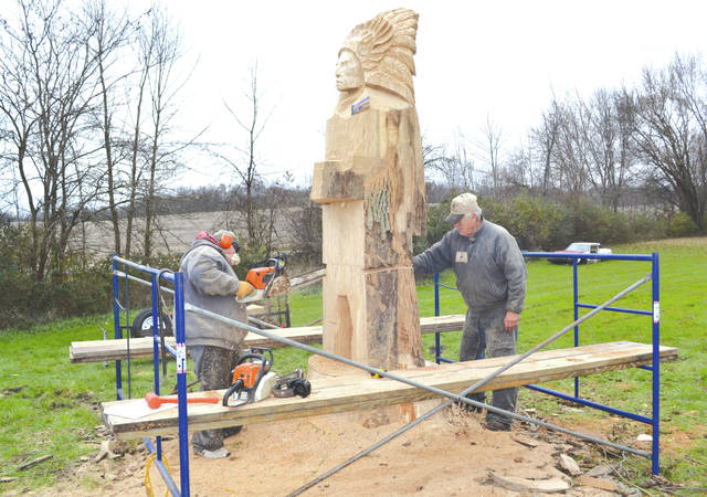 """Pat Holbert and """"Lumber"""" Jack Riese, from Lumber Jack Chainsaw Art, work to transform a dead ash tree on Richard Ludwig's property into a Mechanicsburg Indian on Thursday. The Indian will be visible to all cars passing the property along state Route 161."""