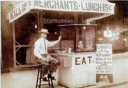 """This 1937 """"Then"""" photo is of the Arch Lunch Stand located in front of the Arch Restaurant at 237 N. Main St., Urbana. Bert L. Plummer, owner, is standing in the window. The person at the lunch stand is unidentified. Mr. Plummer previously had restaurants at 108 S. Main St. in 1914 and at 211 Miami St. in 1930."""