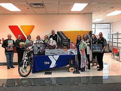 Members of the Silent Auction organizing committee (left to right) Mike Henson, Jill Steinmetz, Beth Harrigan, Polly Long, Chris Phelps, Greg Hower, Nicky Naylor, Billie Jo Fetherolf, Anna Casey, and Jerry Fetherolf pose with a small sampling of items up for bid.